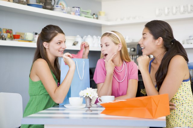 Three young woman sitting at a table taking a break from shopping