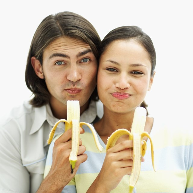 portrait of a young couple eating bananas