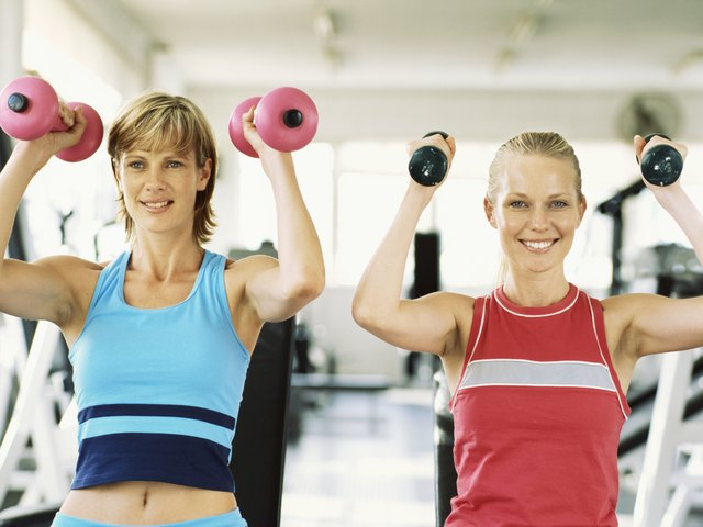 Two young women exercising with dumbbells in the gym