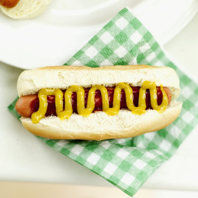 Close-up of a hotdog with mustard on a napkin