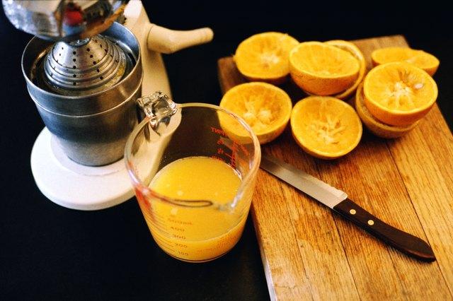 Still life of cut oranges a knife, a juicer and fresh orange juice.