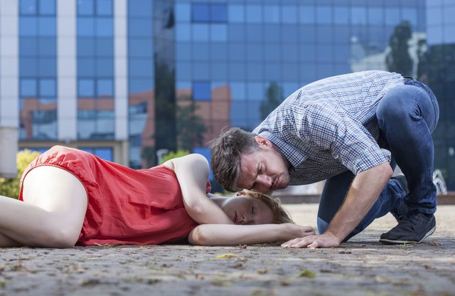 Man checking if woman's breathing