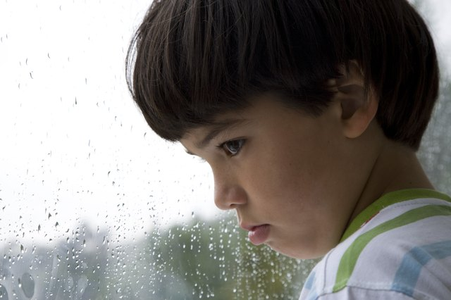 Boy (8-9) looking out window on rainy day