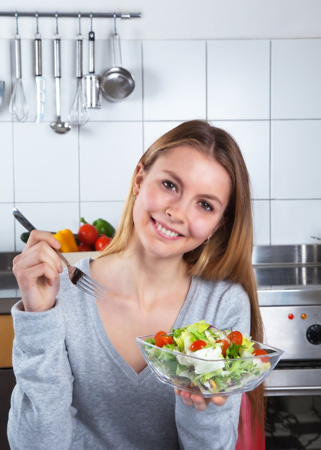 Laughing young woman at kitchen with fresh salad