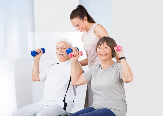 Trainer Assisting Senior Couple With Dumbbells