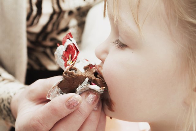 little girl eating chocolate candy. Pleasure.