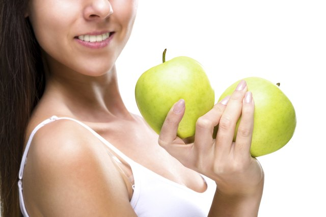 Healthy lifestyle - woman's hands, two beautiful green apple