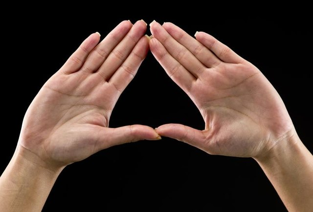 Real people, caucasian woman's hands on black background forming a triangle. In some countries this is a feminist hand sign   (this picture have been shot with a Hasselblad HD3 II 31 megapixels)