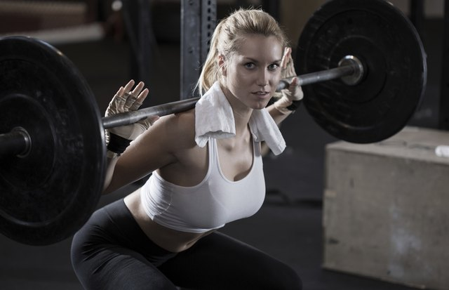 Girl making squat with barbell