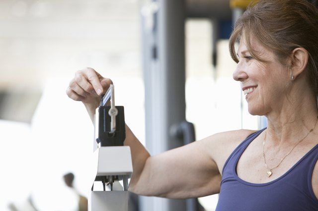senior woman weighing herself at a gym