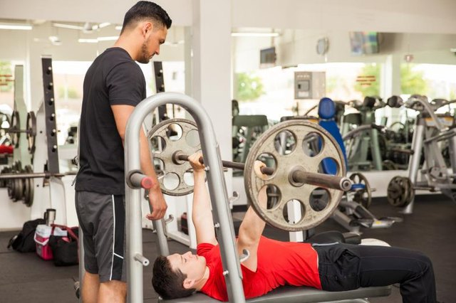 Profile view of a personal trainer spotting a young man while he lifts a barbell on the bench press at a gym
