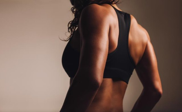 A fit, muscular woman in a sports bra shows off her lats.