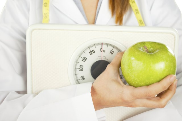 nutritionist holding a green apple and weight scale
