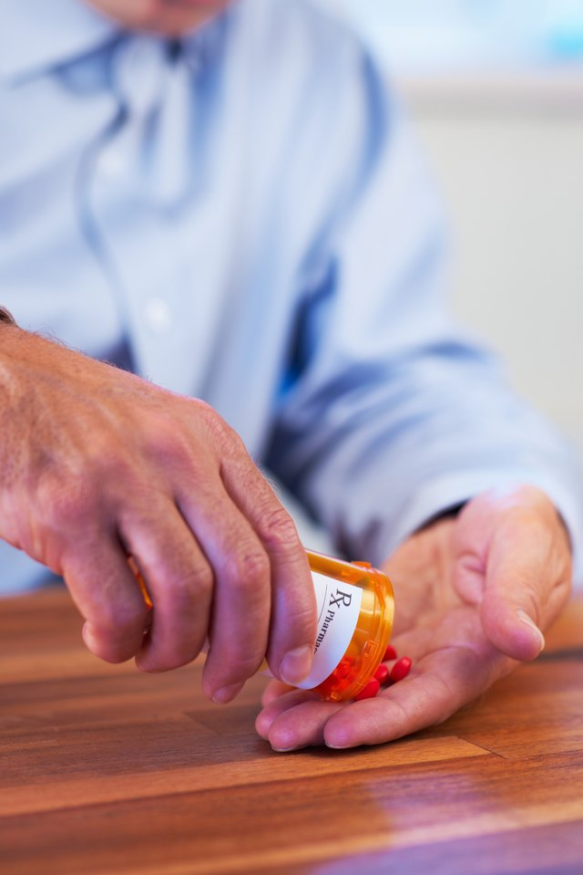 Patient pouring out RX pills into hand