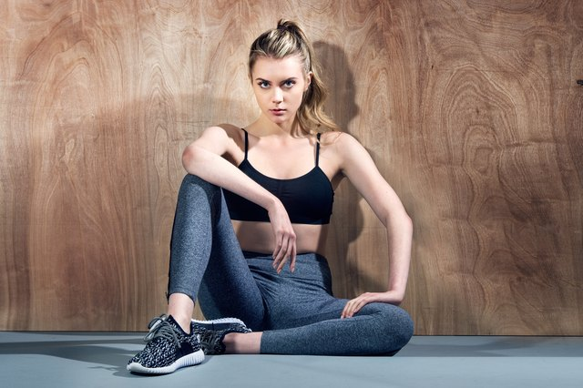 Beautiful fitness girl relaxing after workout in the gym and sitting near the wall.