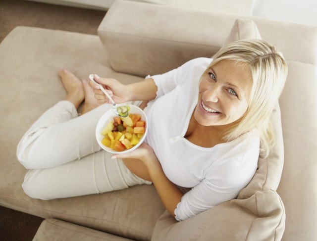Top view of a relaxed mature woman on couch eating