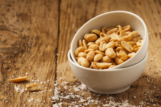 Roasted peanuts and salt in a bowl on wooden background