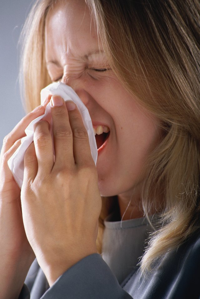 Woman sneezing, holding tissue to nose