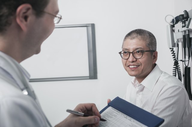 Doctor writing on medical chart with a smiling patient