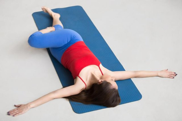 Beautiful happy young woman in bright colorful sportswear working out indoors on blue mat. Girl lying in Reclining Spinal Twist, Jathara Parivartanasana, resting after practice, full length, top view