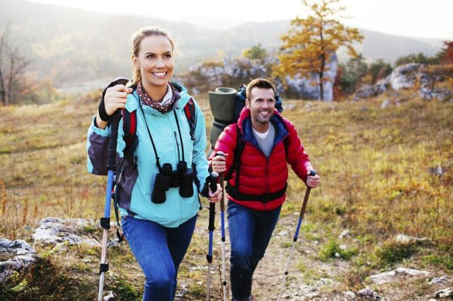 Man and woman wearing hiking gear going atop a mountain.