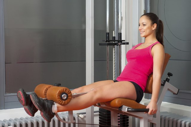 Smiling girl exercising legs in the gym