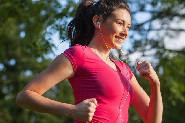 Cheerful young woman jogging in a park