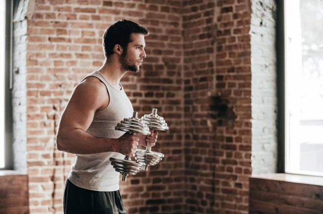 Side view of confident muscled young man wearing sport wear and exercising with dumbbells in loft interior
