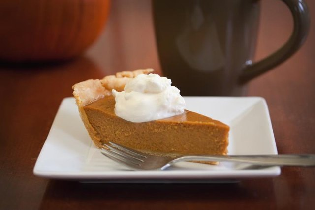 A slice of pumpkin pie with a daub of whipped cream on a white square plate with a fork and coffee cup.