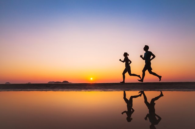 workout, silhouettes of two runners on the beach at sunset, sport and healthy lifestyle background