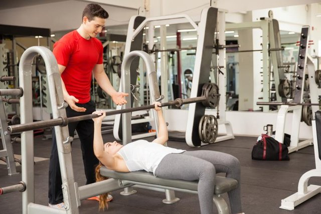 Young athletic woman lifting a barbell on a bench press while her personal trainer spots her at a gym