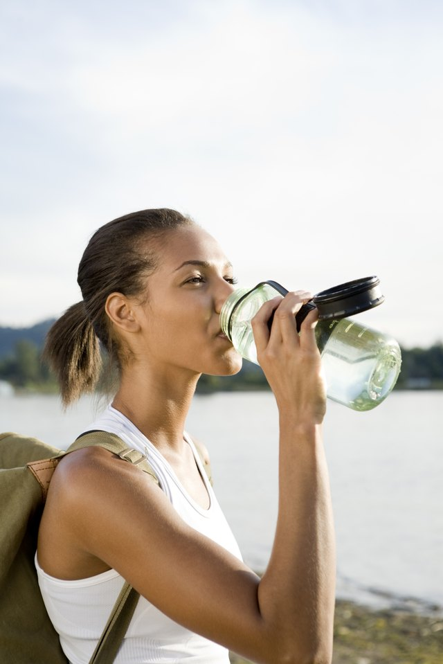 Athletic, thirsty hiker in sportswear drinking from water bottle and hiking in remote area