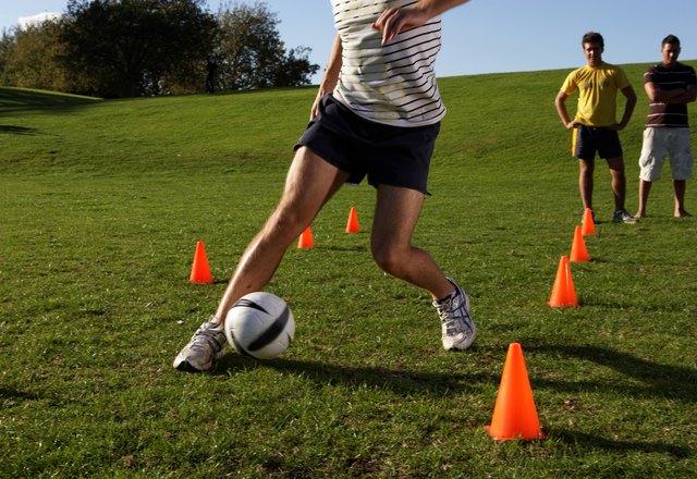 Men practising football, dribbling through cones in field