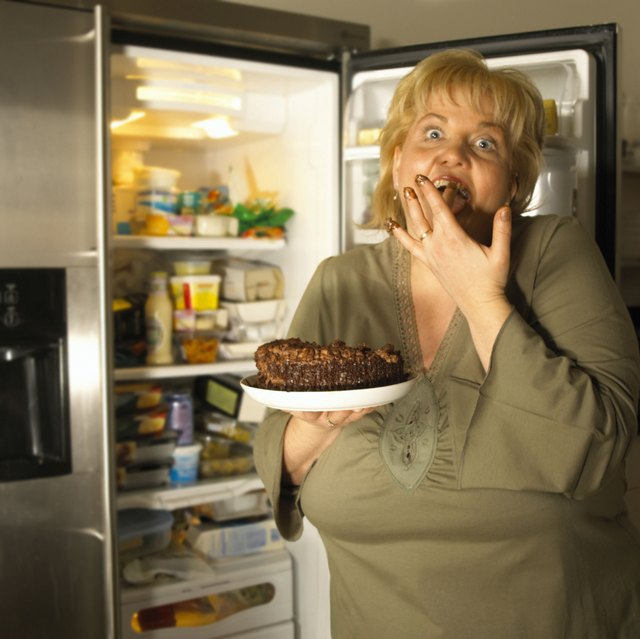 Woman shoving cake in her mouth