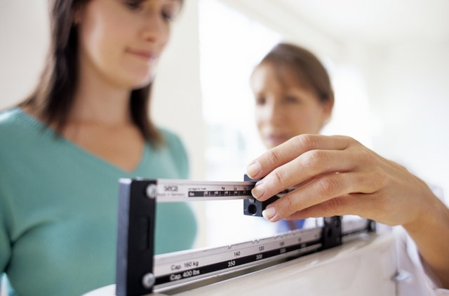 Doctor adjusting balance on weighing scale while patient checking weight