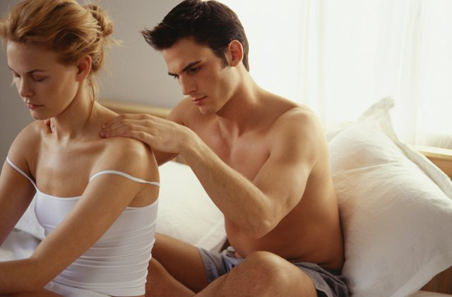 Couple sitting in Bed, Man Massaging shoulders of woman
