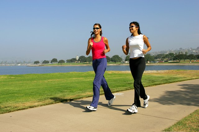 Two women jogging on the seafront.