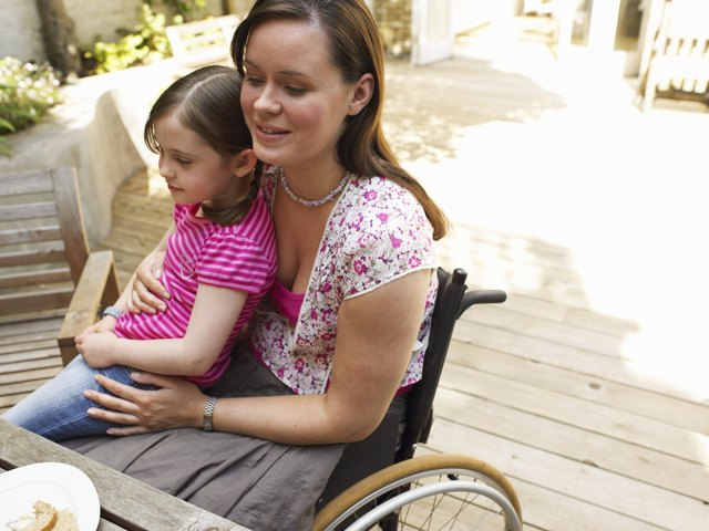 Woman sitting in wheelchair, with daughter (6-8) on lap, smiling