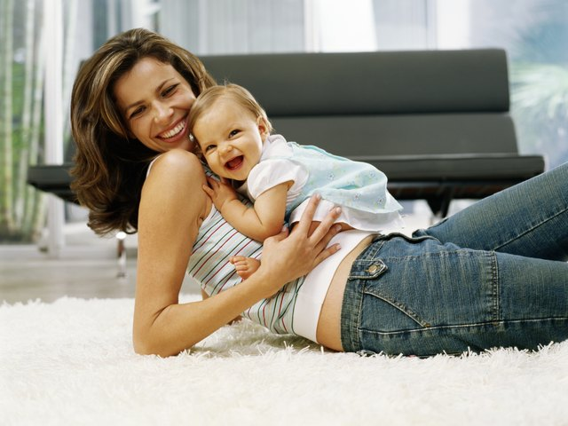 Baby girl (6-9 months) sitting on reclining mother, laughing, portrait