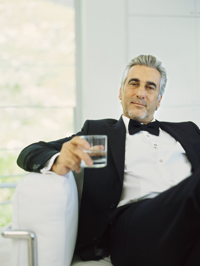 Portrait of a mature man in a tuxedo holding a glass of water