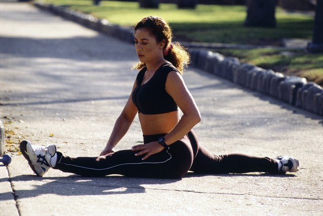 Woman doing the splits warming up in a park
