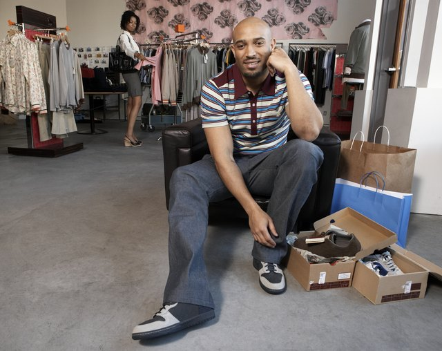 Man trying on shoes in retail store, woman shopping in background