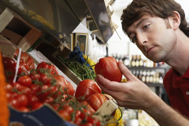 Young man in shop examining large tomato, close-up