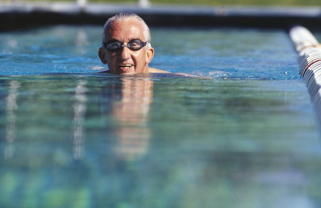 Senior man swimming in outdoor pool, surface view