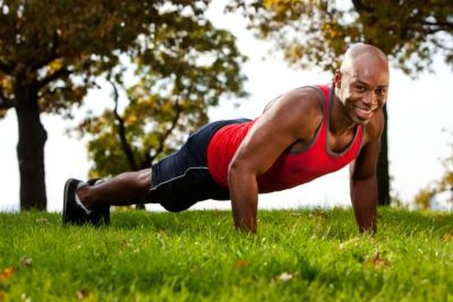 A smiling man does a push-up exercise outdoors at the park.