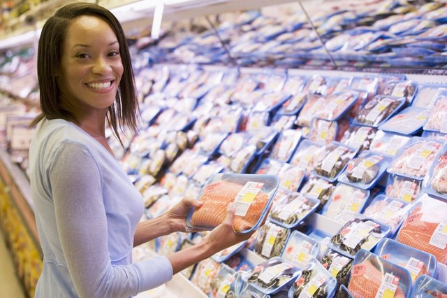 Woman shopping for fish and seafood at a grocery store