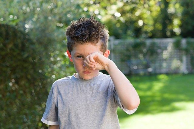 Boy rubbing eye