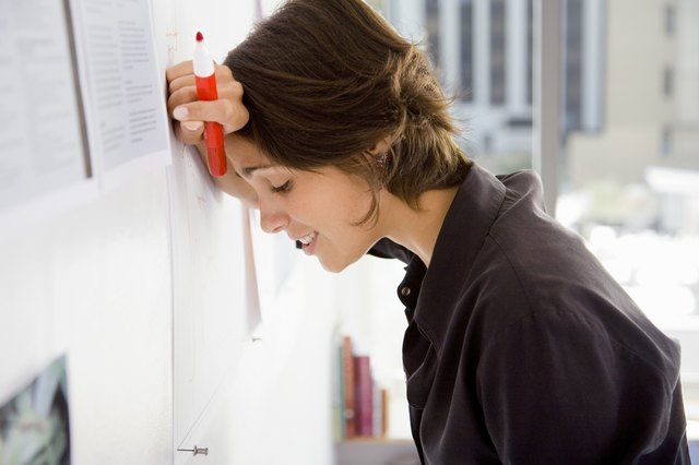 Businesswoman with marker leaning head against wall