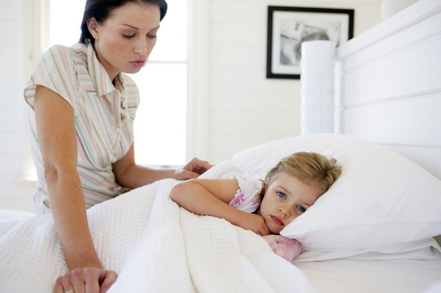 Mother sitting with daughter in bed