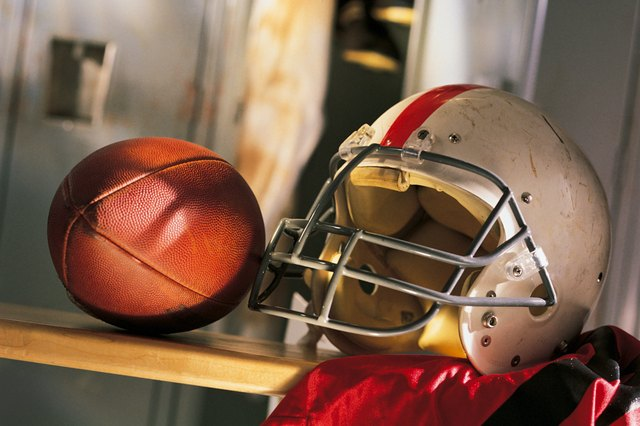 Football and helmet with jersey on locker room bench